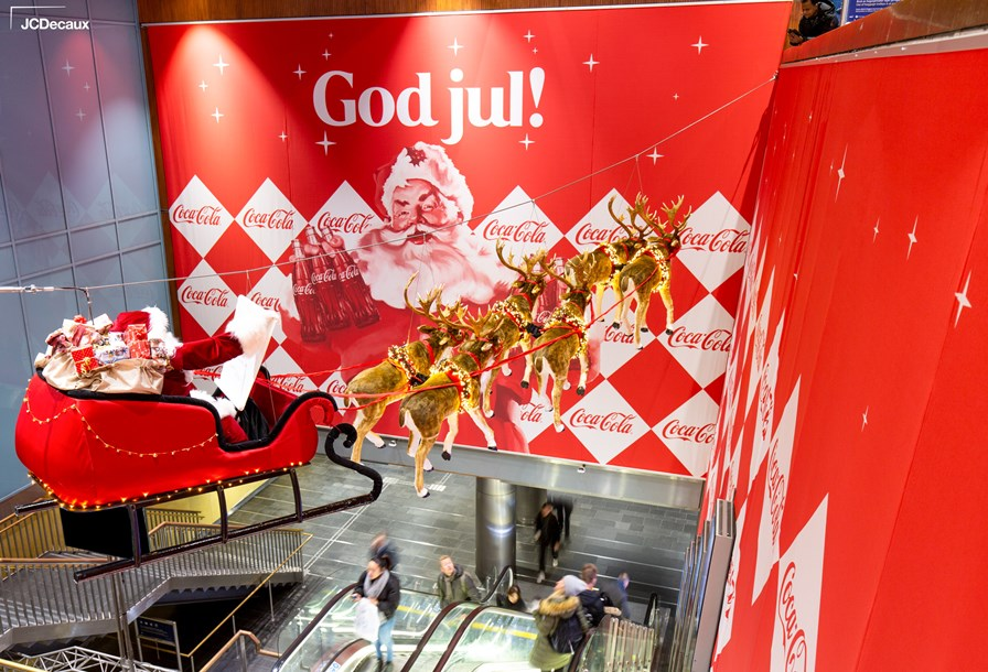 JCDecaux Norway | Station Domination | Coca-Cola | Santa on sleigh with 6 reindeers hanging inside Oslo Central Station. This installation had music (coca jingle), 300sqm of banners and floor graphics with 100% SOV on the digital escalator panels.